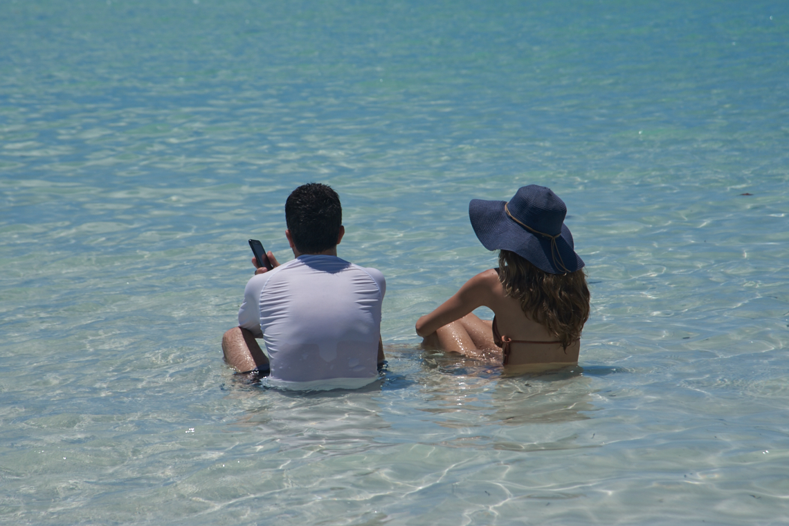 two people on phones in the sea sitting